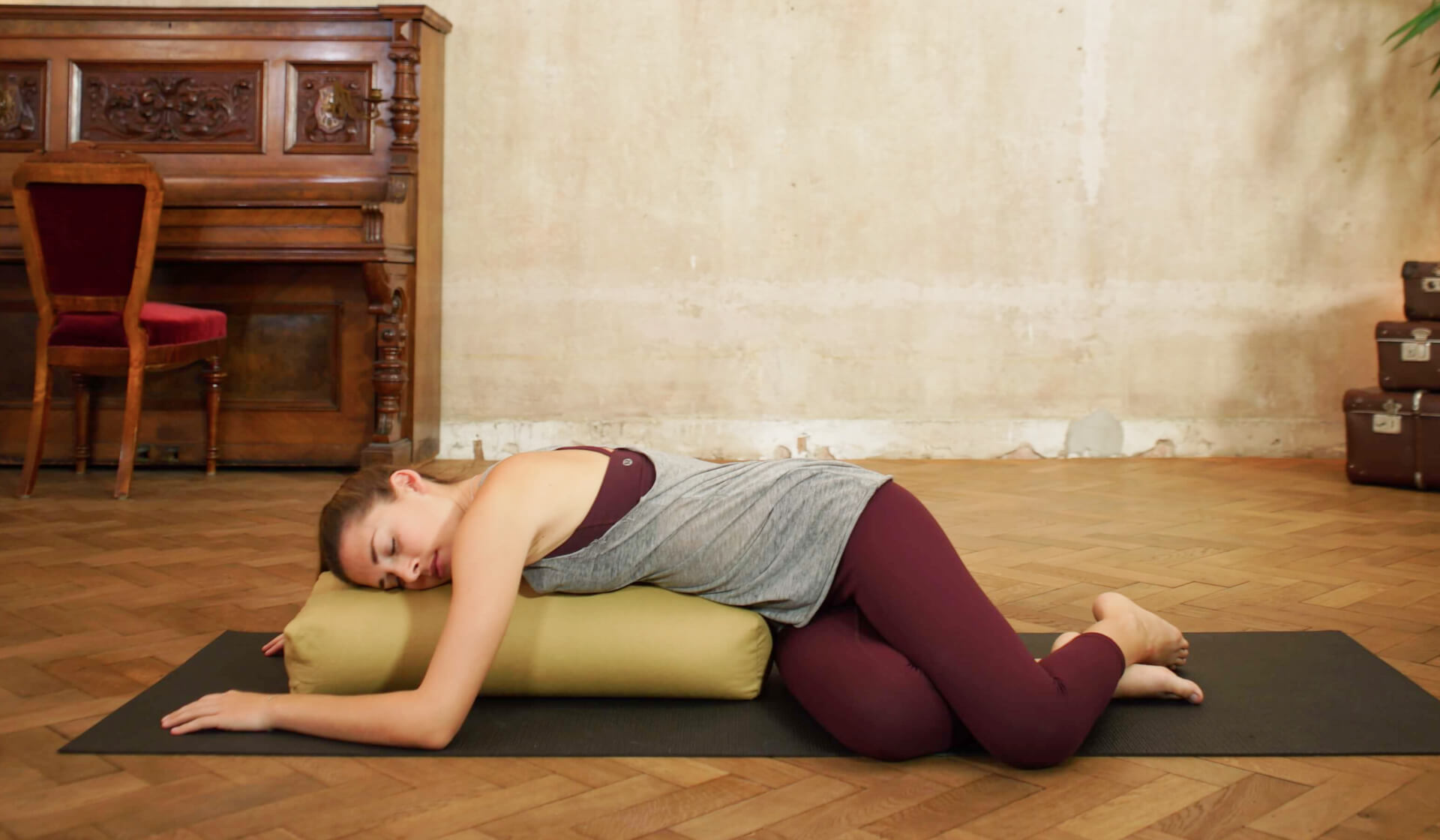Yoga teacher practicing a relaxing restorative yoga pose laying over a bolster in front of a beige wall and piano