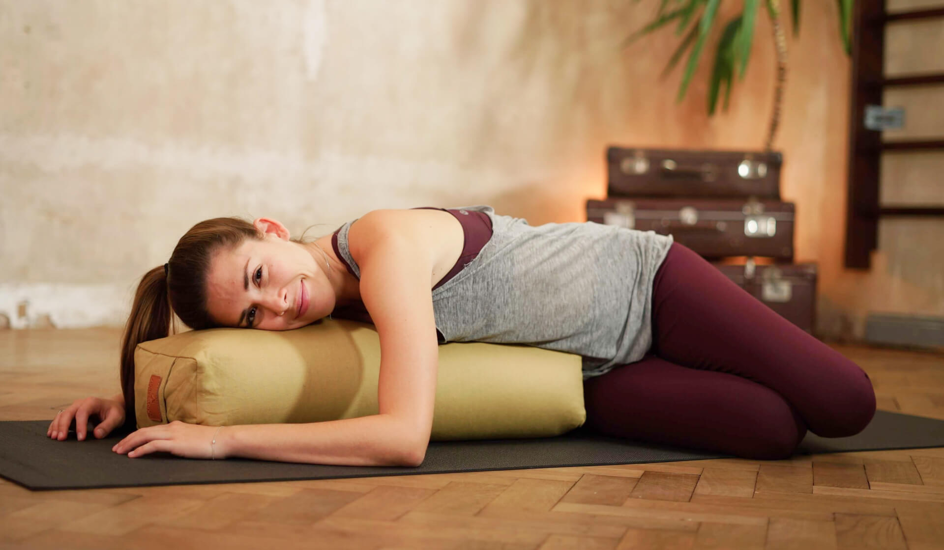 Yoga teacher practicing a relaxing restorative yoga pose - side lying over a yoga bolster and smiling