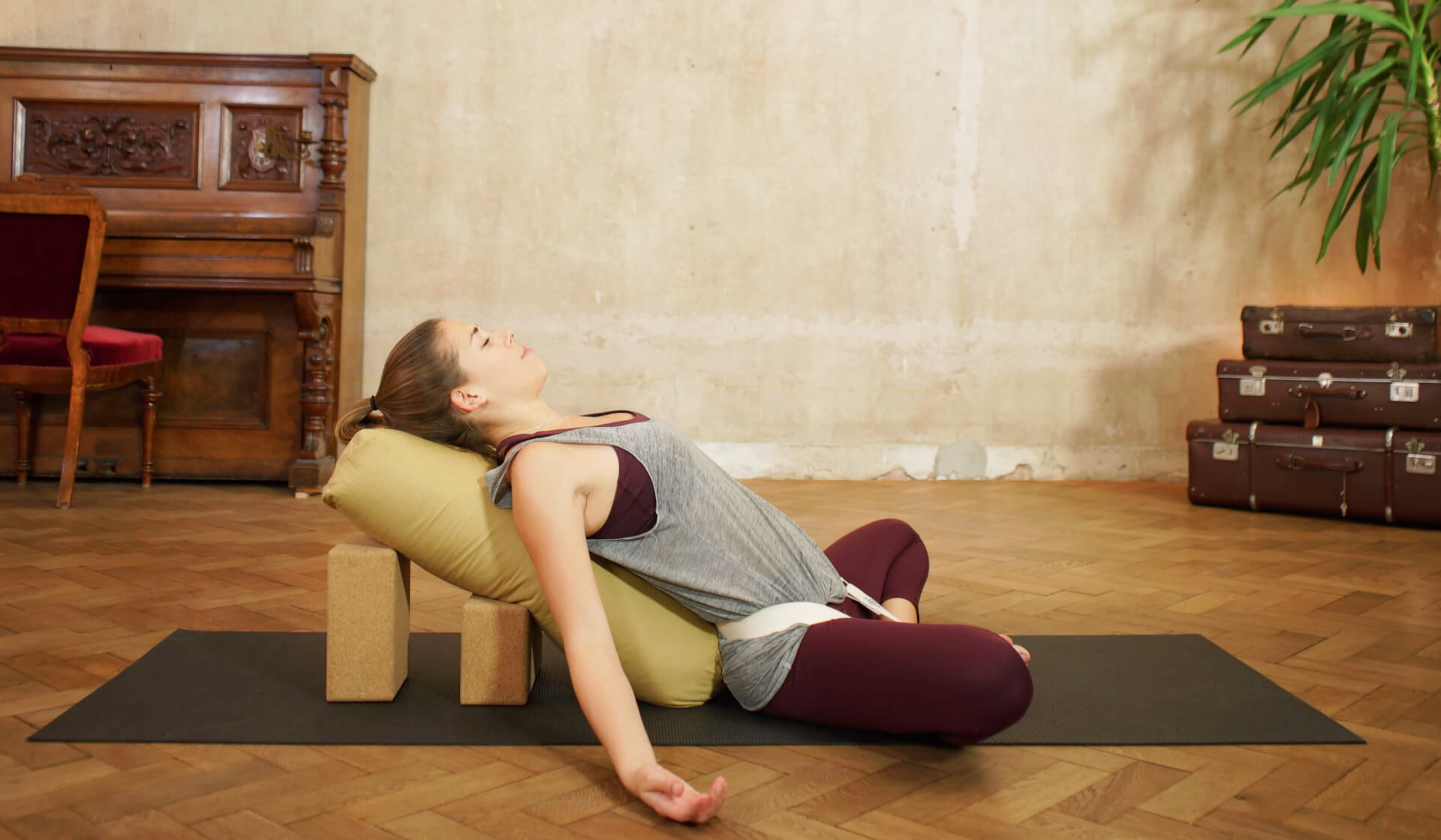 Yoga teacher relaxing in a restorative yoga pose laying over a bolster and blocks with a strap wrapped around her legs