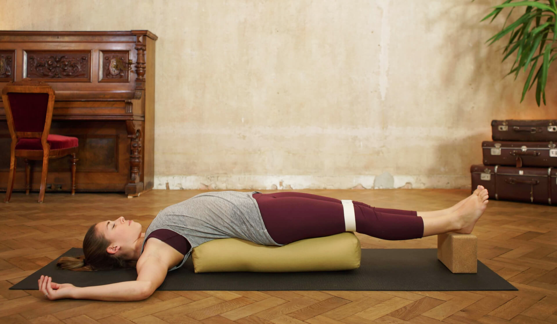 Yoga teacher relaxing in a restorative yoga pose, laying over a biege bolster and blocks in front of a piano