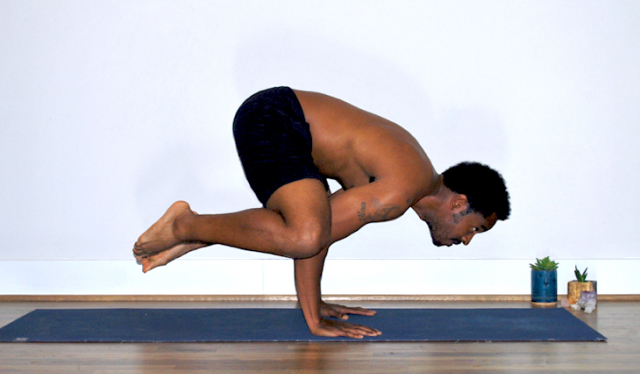 Man practicing crow pose (bakasana) in black shorts with no shirt on a navy blue yoga mat in front of a white wall