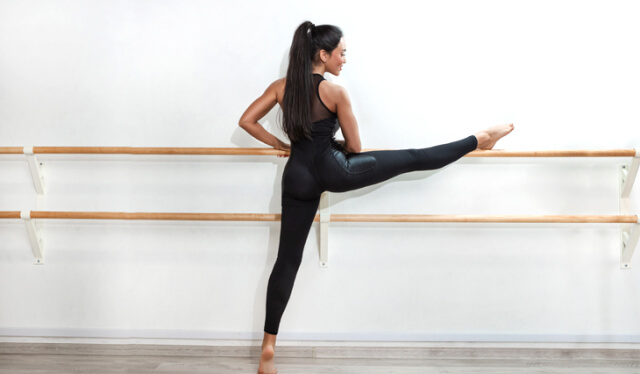 Woman dressed in all black in a splits position with her right leg up on a ballet barre in front of a white wall