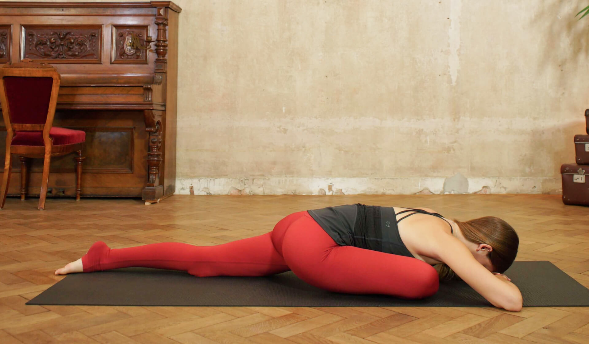 Yoga teacher in black tank top and red yoga pants folding forward into pigeon pose on a black yoga mat in front of a piano and beige wall