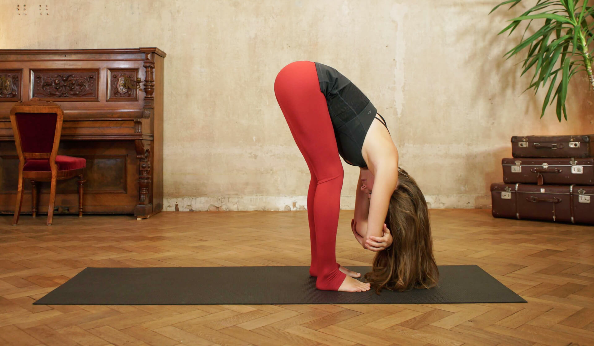Female yoga teacher in a black tank top and red yoga pants folding forward in dangling pose on a black yoga mat in front of a piano and beige wall