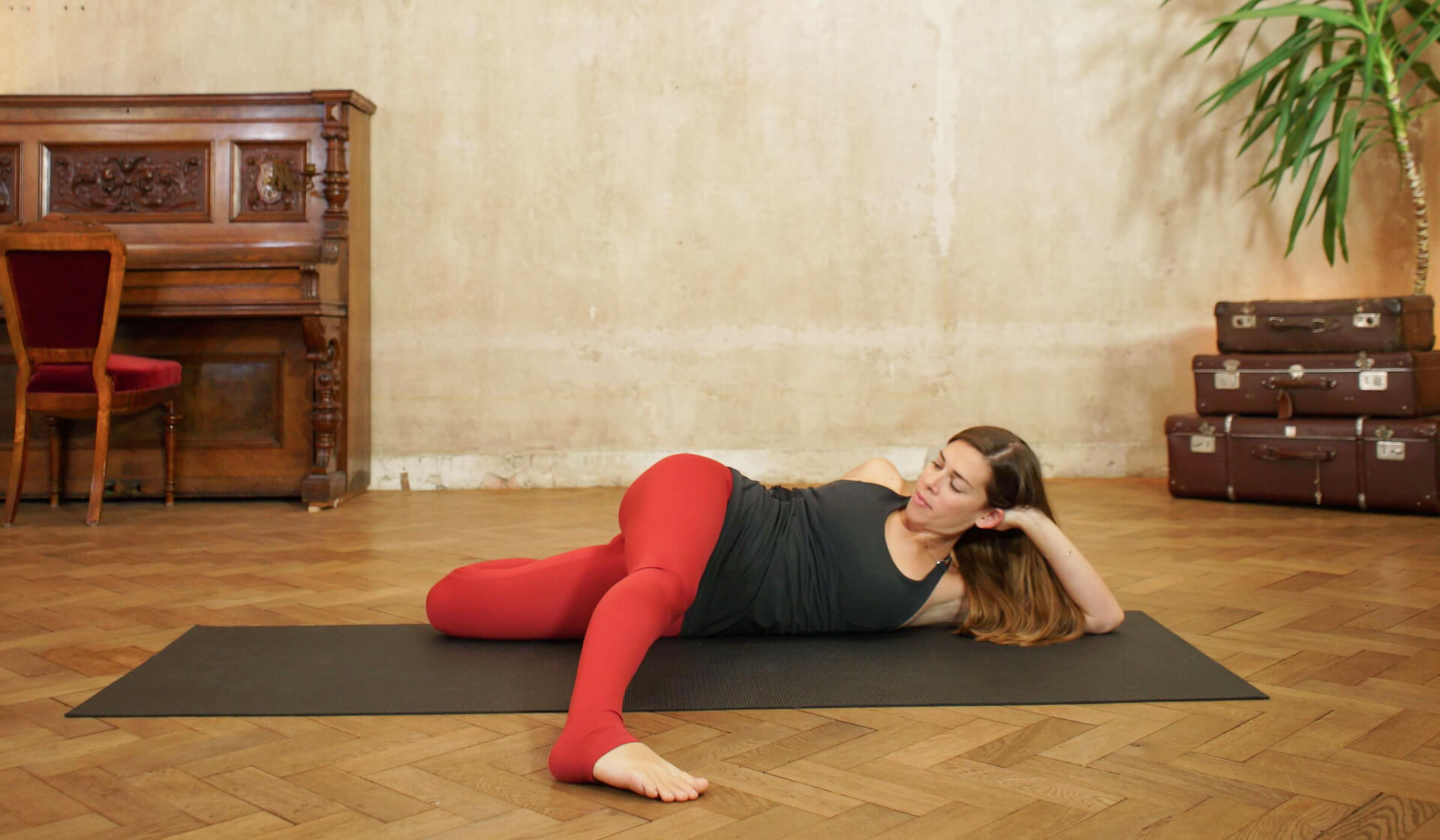 Female yoga teacher in a black tank top and red yoga pants laying on her side and stretching her quads in cat pulling its tail pose on a black yoga mat in front of a piano and beige wall