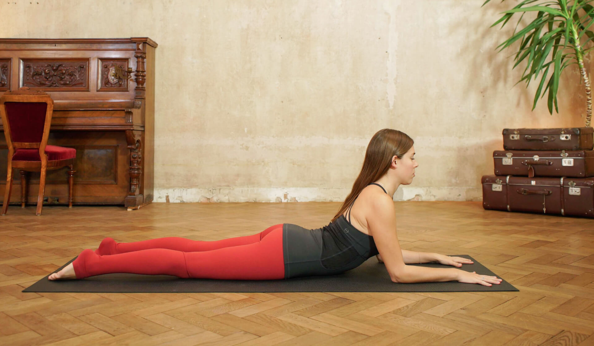 Female yoga teacher in a black tank top and red yoga pants laying on her belly propped up on her forearms in sphinx pose on a black yoga mat in front of a piano and beige wall