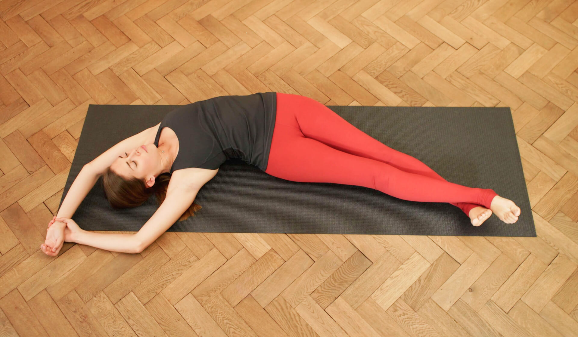 Aerial view of a female yoga teacher in a black tank top and red yoga pants laying on her back doing a side body stretch in bananasana on a black yoga mat