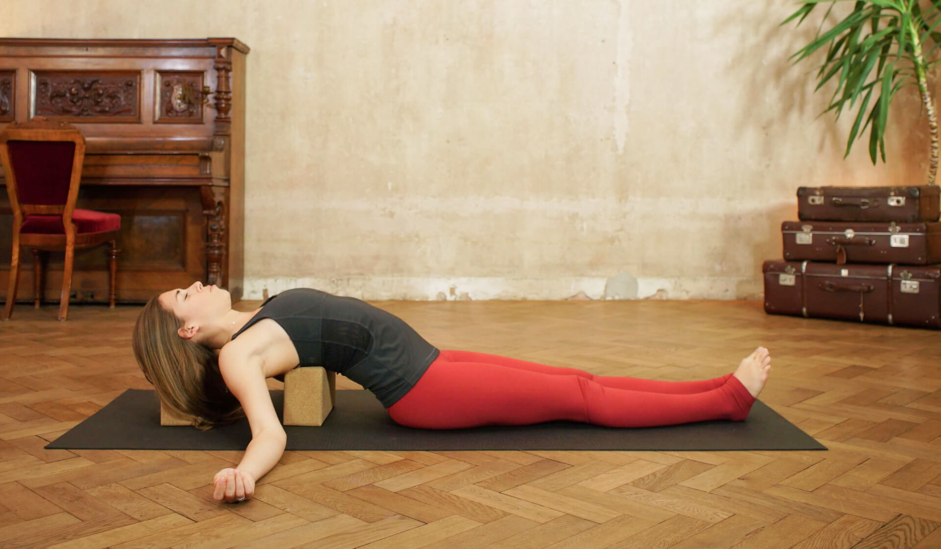 Female yoga teacher in a black tank top and red yoga pants laying back over yoga blocks in supported fish pose on a black yoga mat in front of a piano and beige wall
