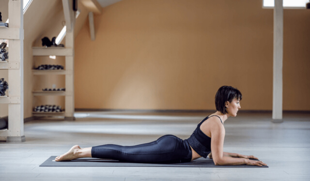 Woman in black yoga clothes practicing the backbend sphinx pose on a black yoga mat in front of a beige wall
