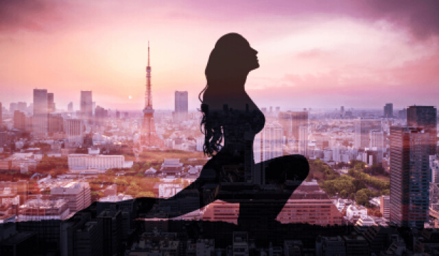 Silhouette of woman practicing a low lunge pose (anjaneyasana) in front of a city landscape with the sun setting in the background