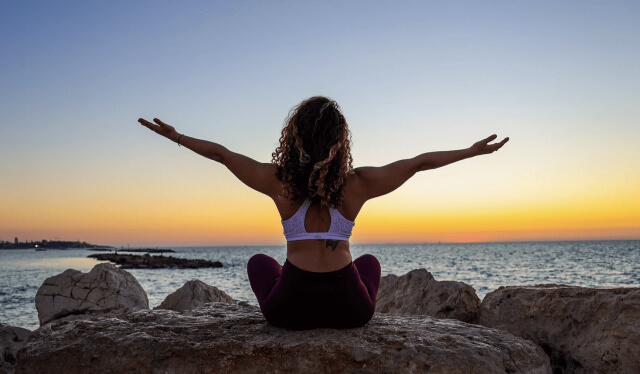Silhouette of a woman sitting on a rock in front of the ocean watching the sunset with her arms open wide