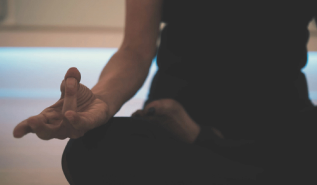 Close up of a person dressed in all black sitting in meditation with hands in jnana mudra