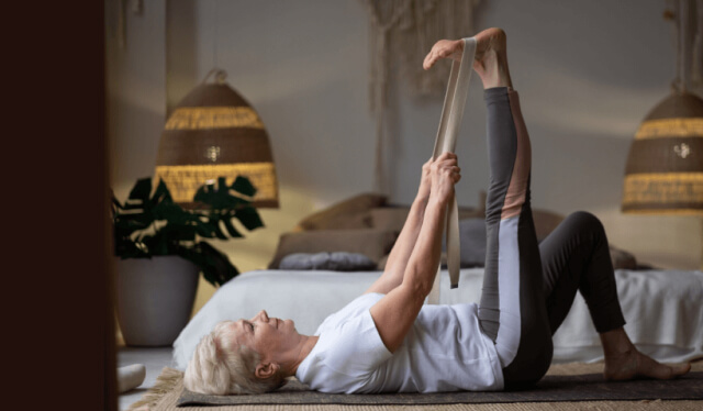 Woman laying on her back in yoga clothes with a strap wrapped around her right foot as she stretches her right hamstrings by reaching her right foot toward the sky