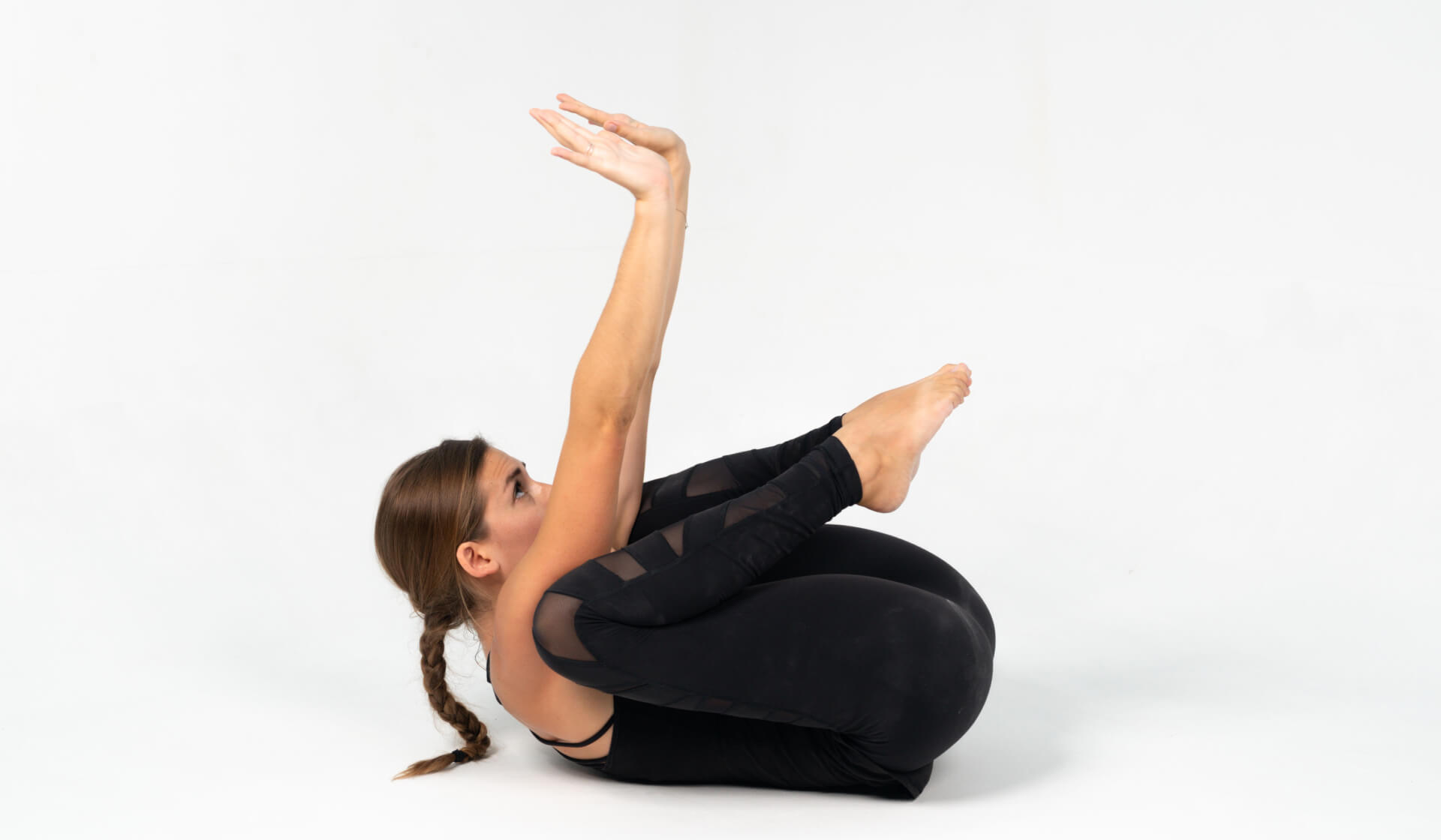 Woman yoga teacher dressed in all black practicing a yoga pose on her back (supine crow pose or supta bakasana) against a white backdrop