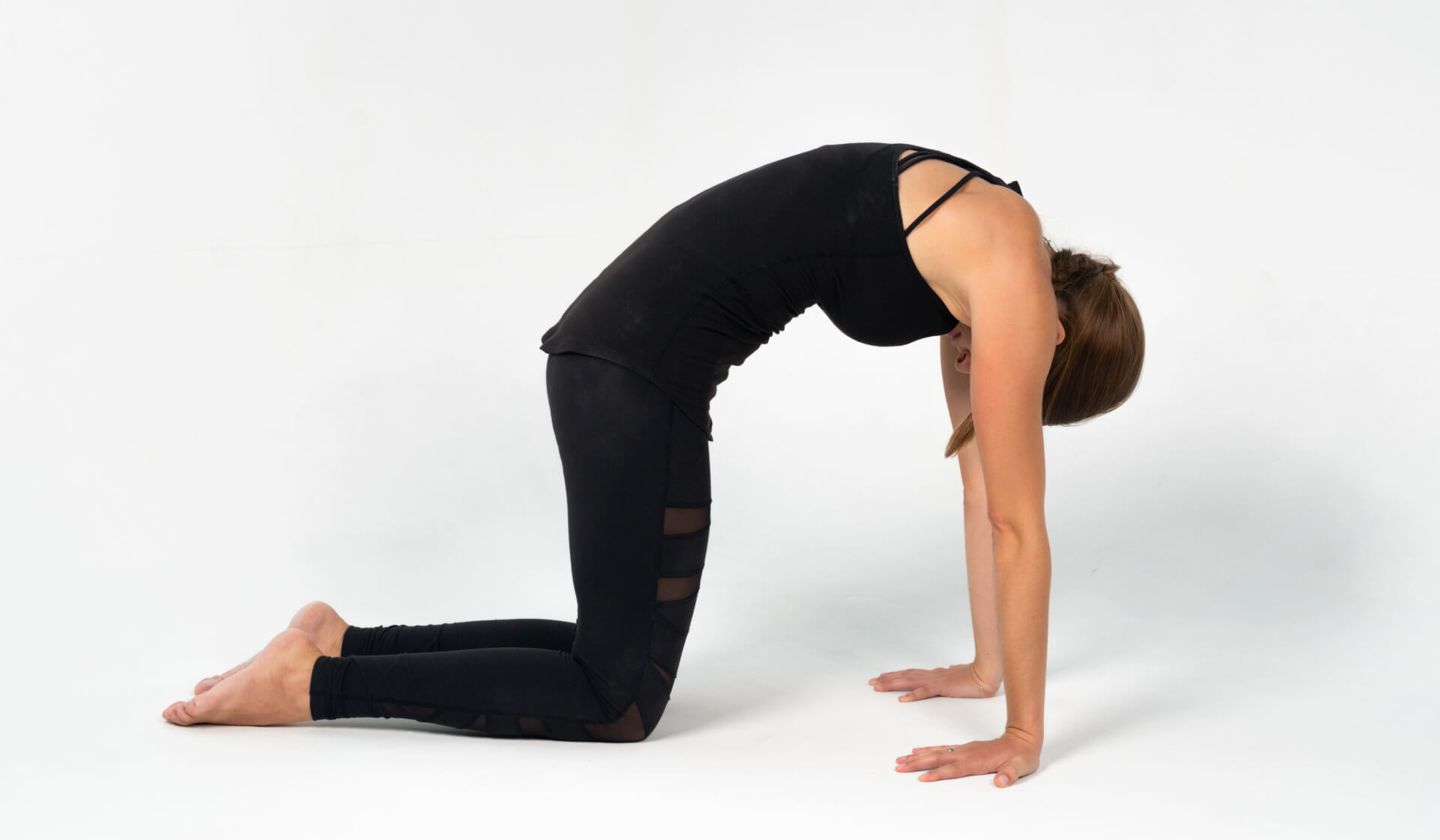 Woman yoga teacher dressed in all black practicing a yoga pose on all fours (cat pose) against a white backdrop