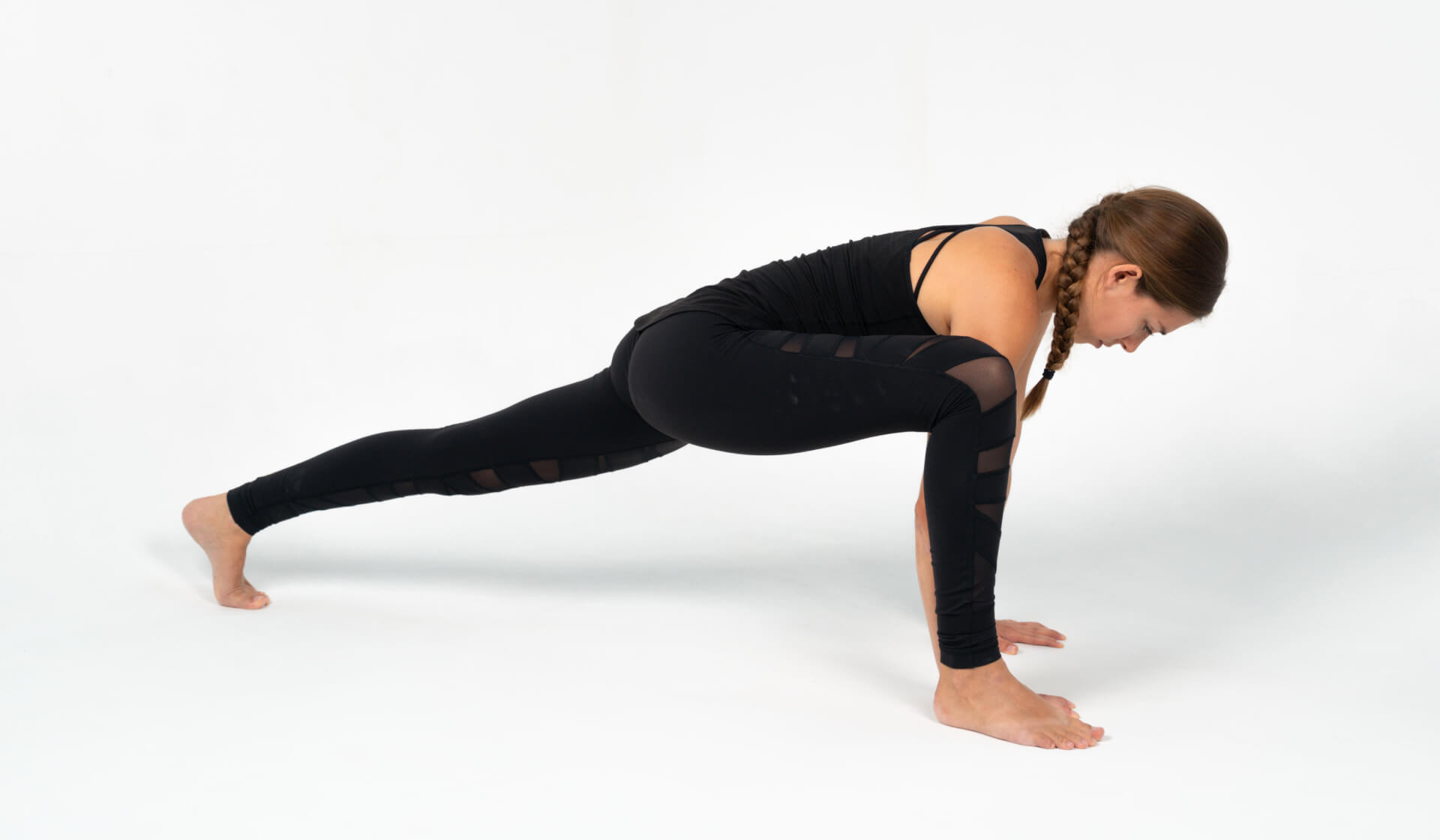 Woman yoga teacher dressed in all black practicing a yoga lunge pose (lizard pose) against a white backdrop