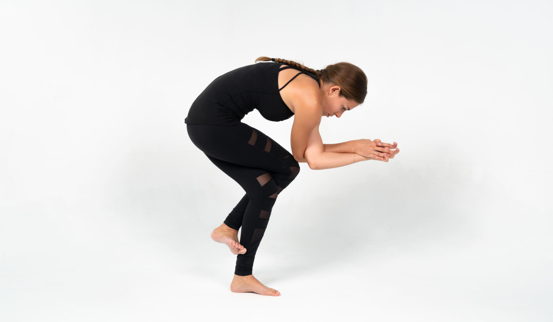 Woman yoga teacher dressed in all black practicing a balancing yoga pose (sleeping eagle pose or garudasana) against a white backdrop