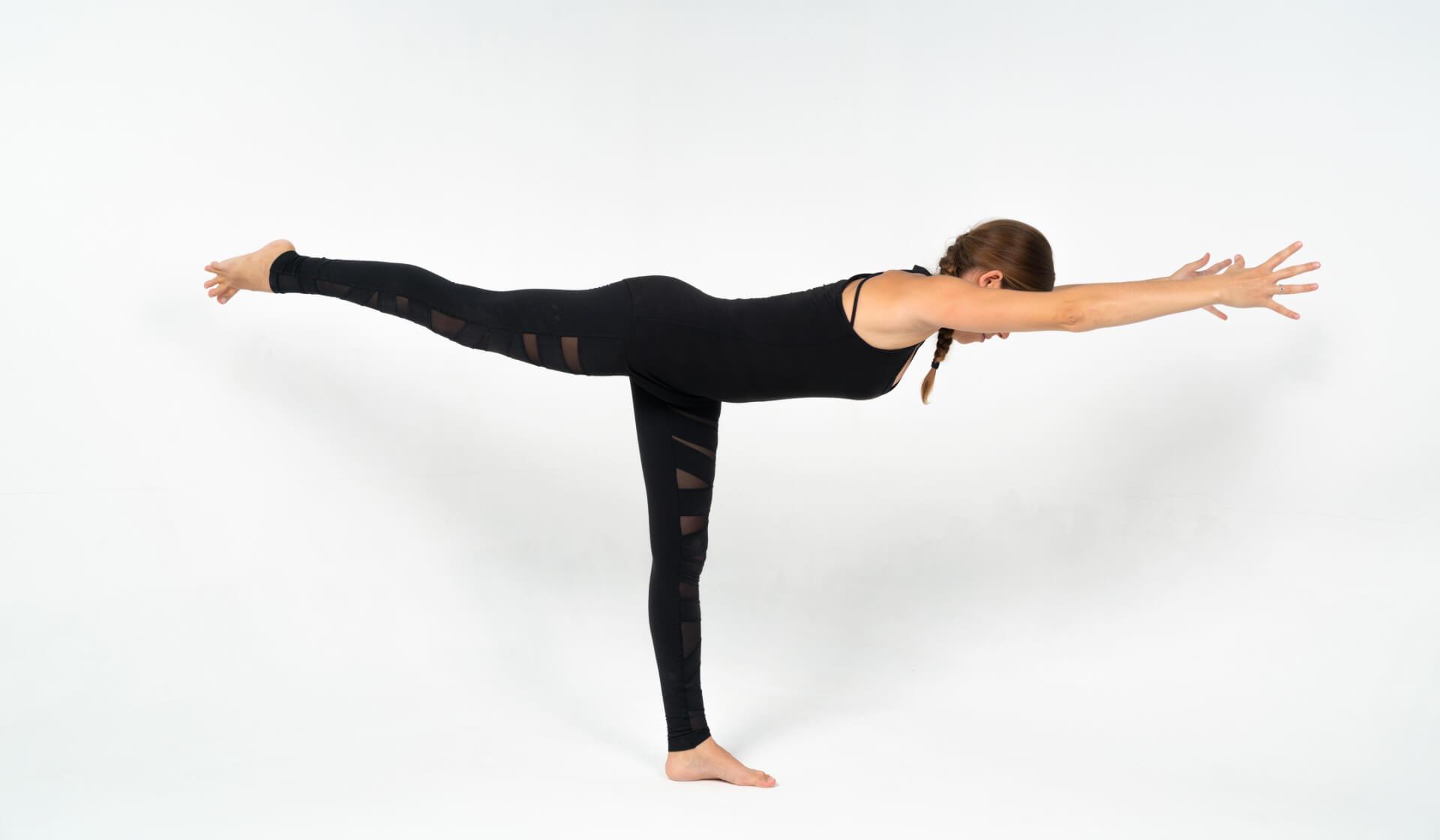 Woman yoga teacher dressed in all black practicing a balancing yoga pose (warrior III or virabhadrasana III) against a white backdrop