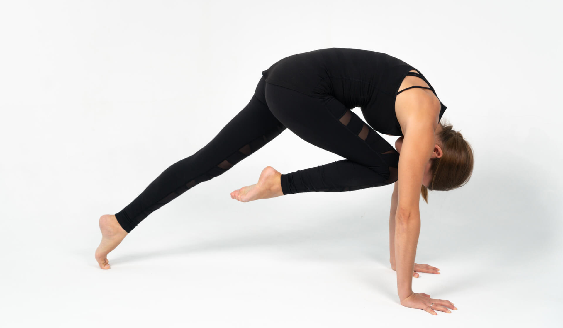 Woman yoga teacher dressed in all black practicing a yoga pose (core plank pose) against a white backdrop