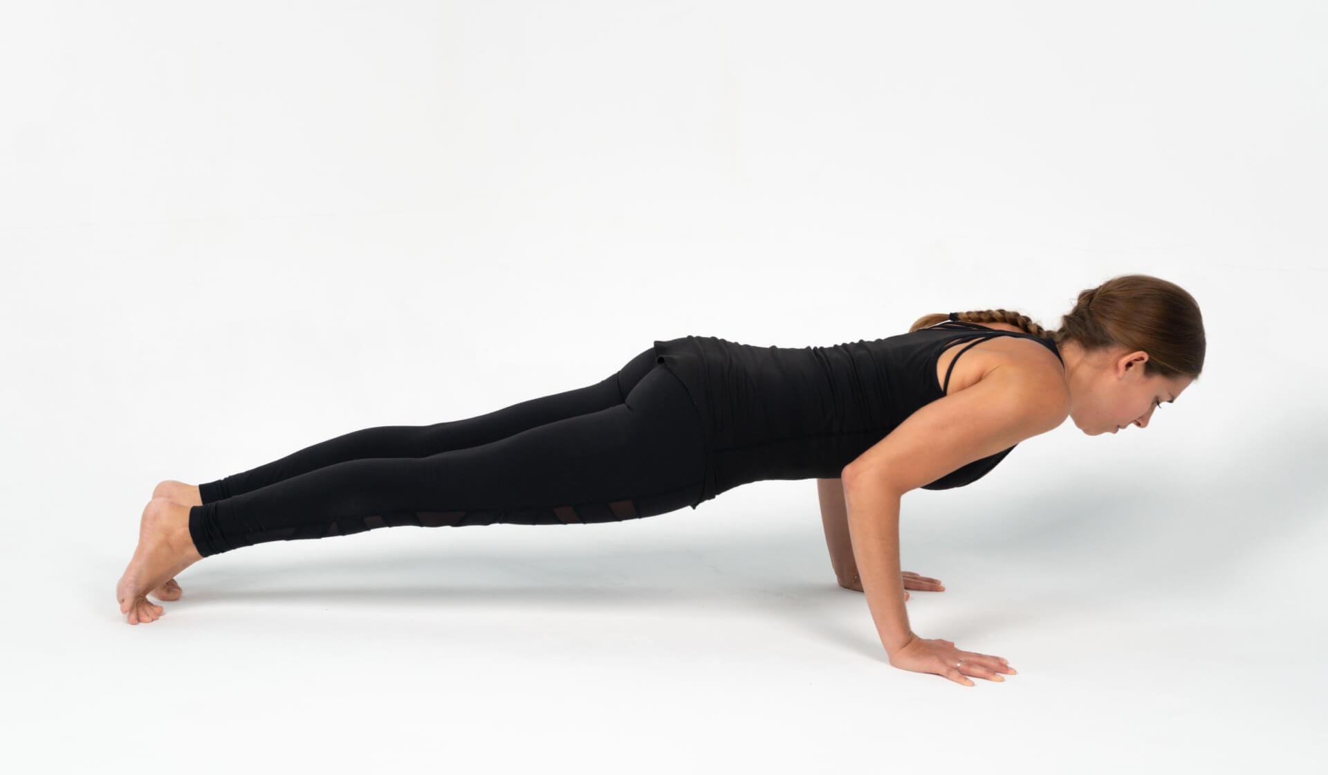 Woman yoga teacher dressed in all black practicing a yoga pose (chaturanga dandasana or yogic push-up) against a white backdrop