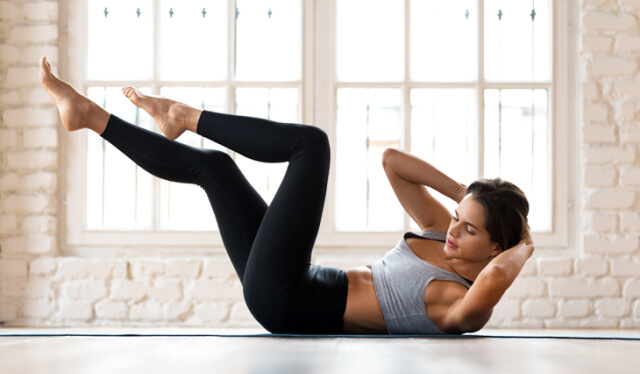 Woman in a gray sports bra and black leggings lying on her back doing a bicycle crunch ab exercise in front of a bright window