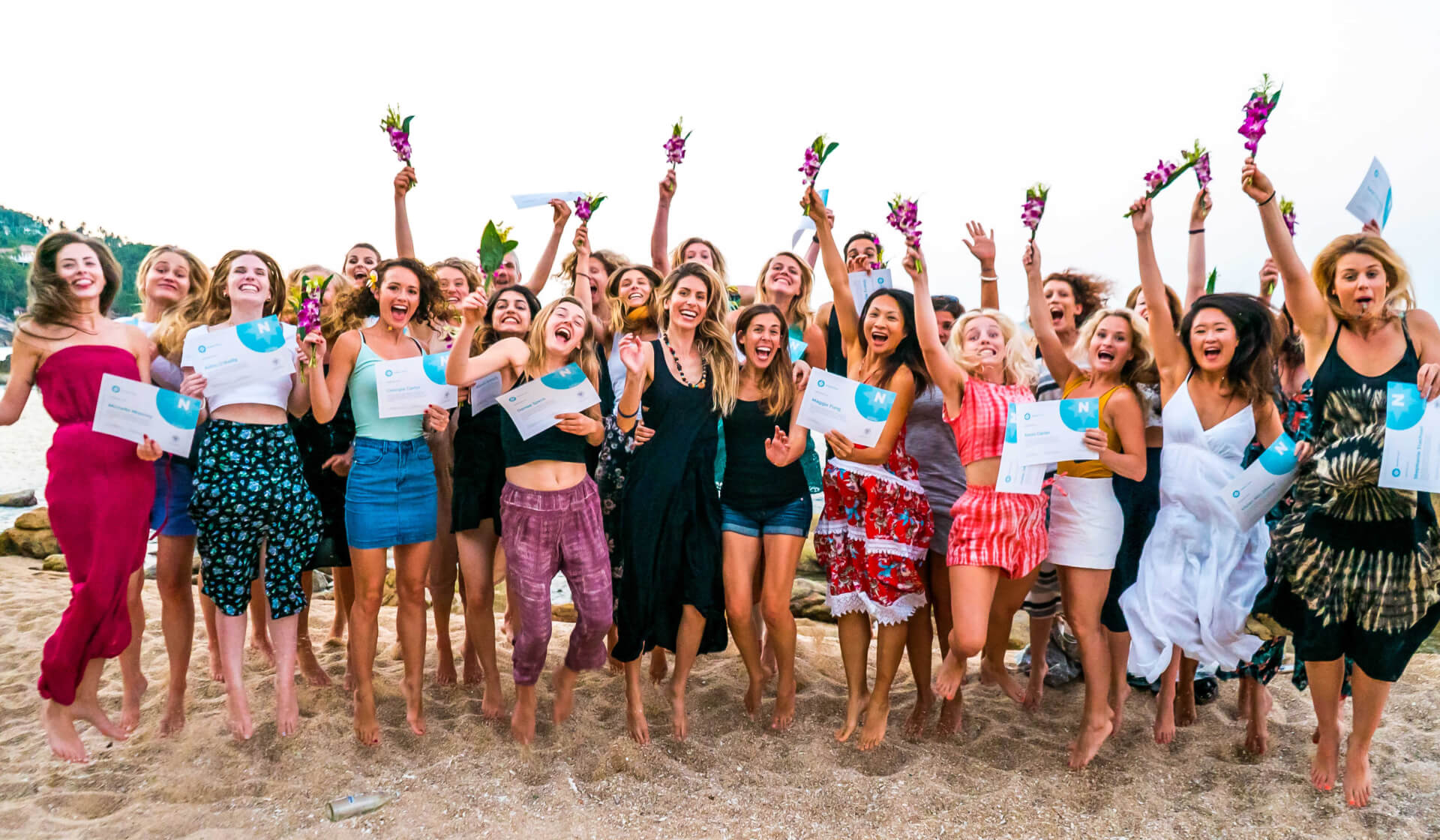 Group of yoga teacher training graduates holding their new YTT certificates and flowers, jumping in the air to celebrate their graduation on a beach