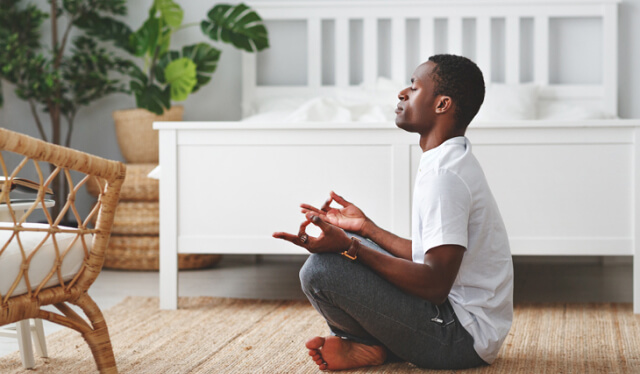Man sitting in a seat of meditation on the floor with his eyes closed and holding his hands in a mudra in front of a white bed