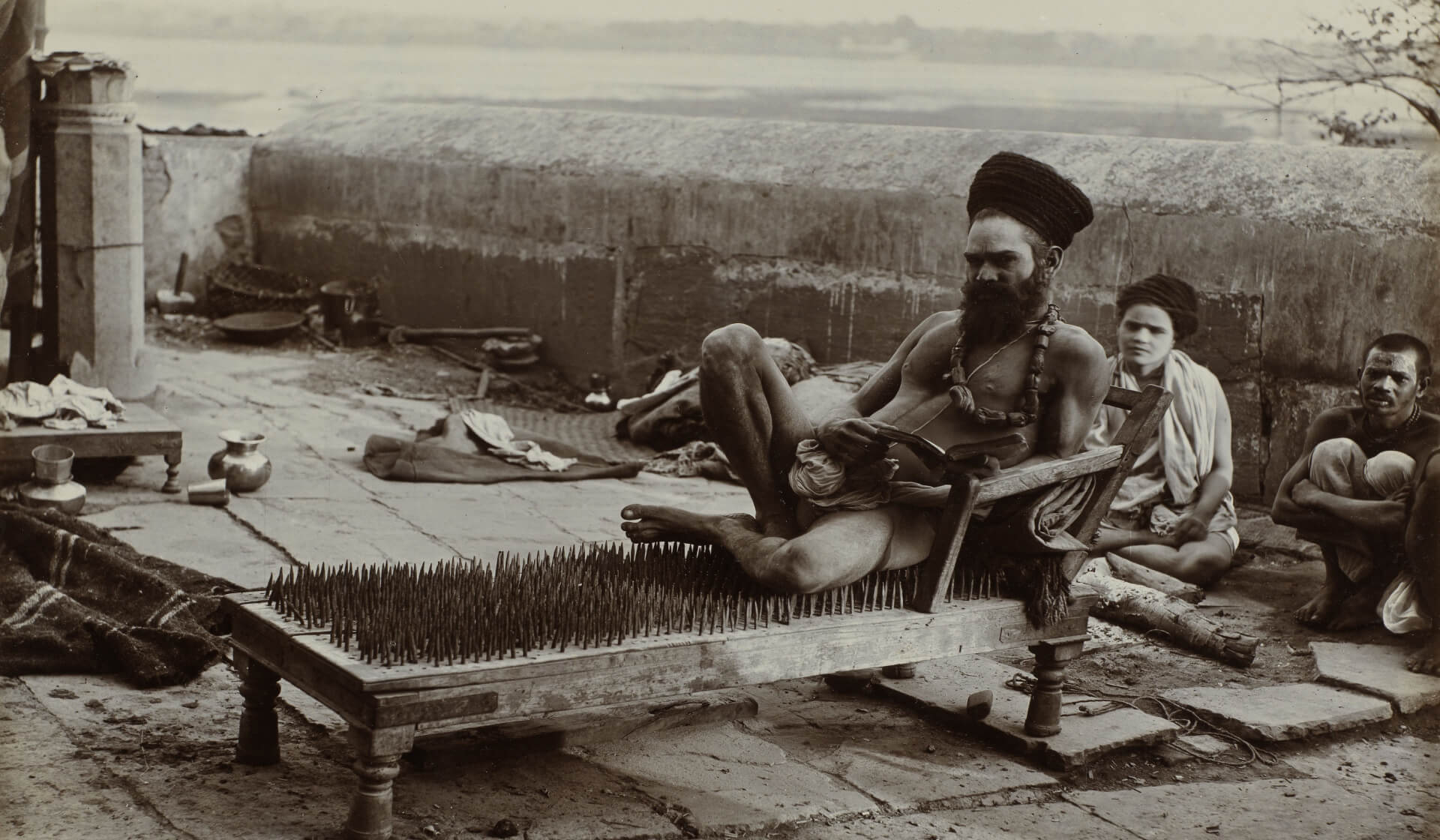 Yogi wearing a turban and a loincloth reclining while reading a book sitting on a bed of nails with two yogis looking on in the background