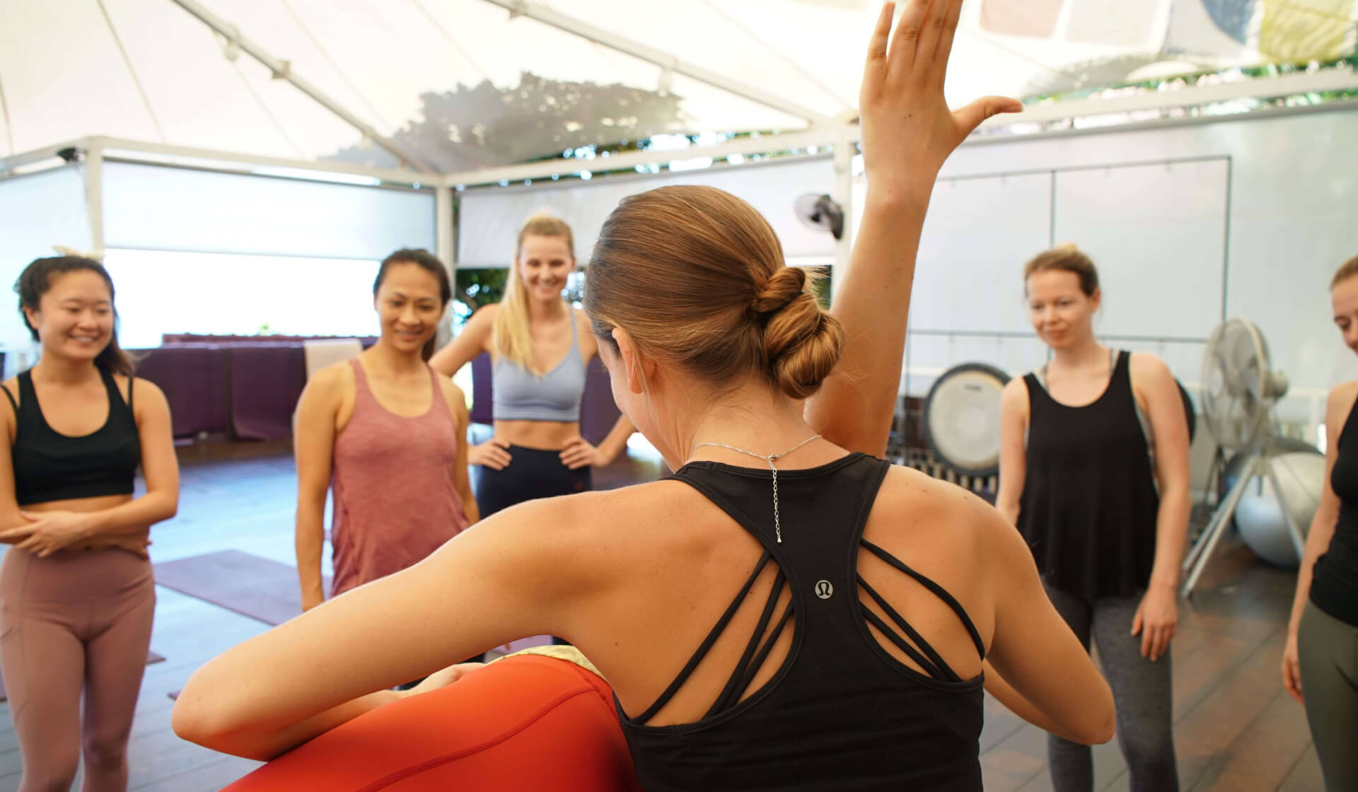 The backside of a yoga teacher assisting a student in a yoga pose with a group of yoga teacher trainees watching and learning the hands-on assist in a yoga shala