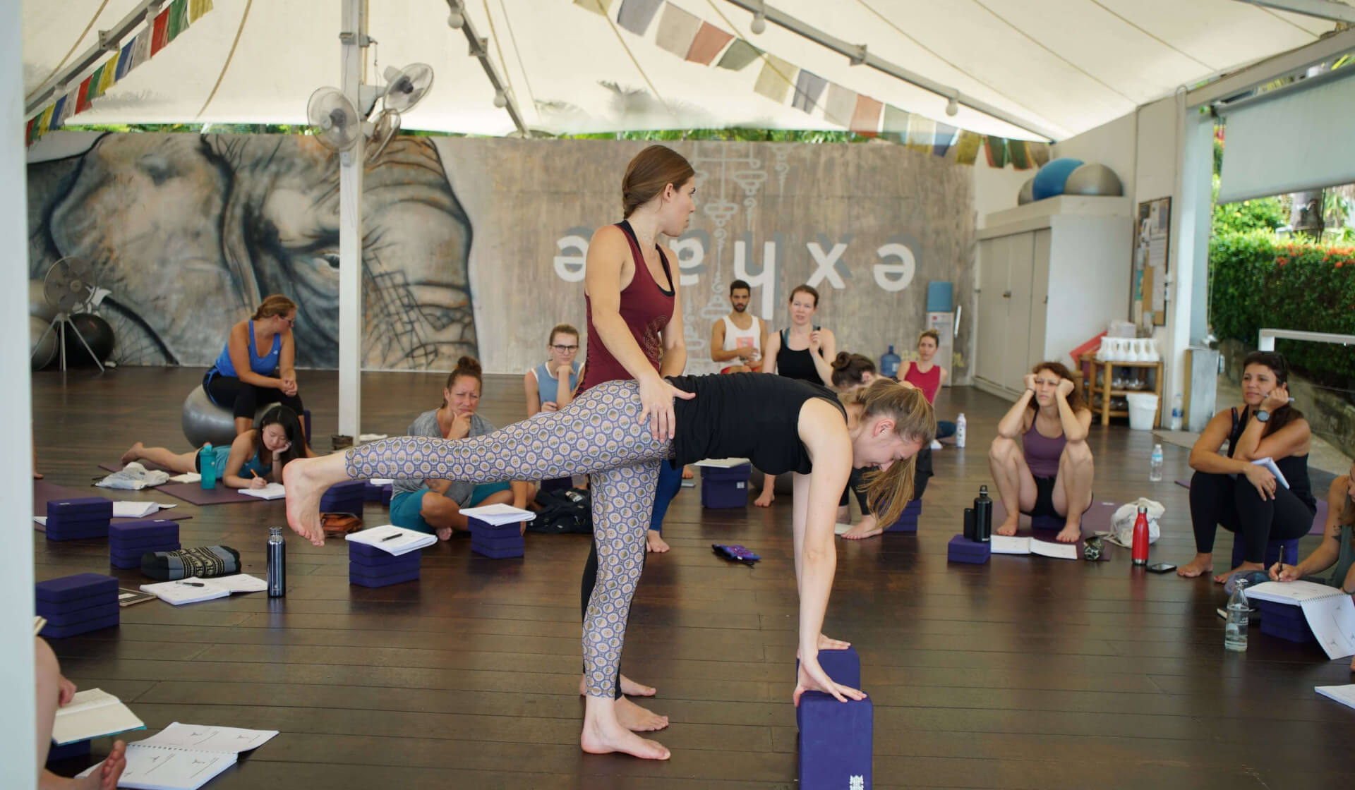 Yoga teacher trainer showing onlooking students how to offer a hands-on assist in Warrior III in an open-air yoga shalaa