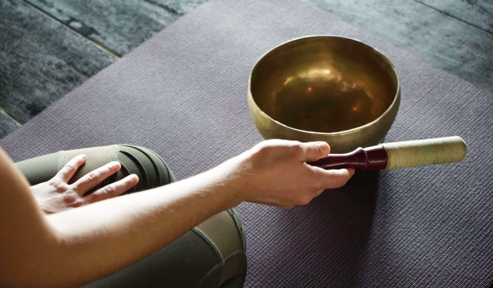 Close up of a yoga mat with a Tibetan singing bowl on it and a yoga teacher's hand striking the singing bowl to make sound