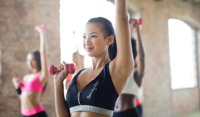 Three women in sports bras holding dumbbells and reaching their arms overhead in a barre workout class