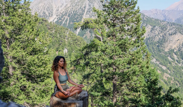 Woman sitting in a seat of meditation with her eyes closed on a tree stump in front of a mountain and forest trees