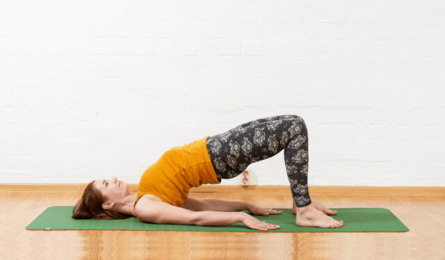 Woman in an orange shirt and black floral leggings practicing bridge pose on a green yoga mat in front of a white wall