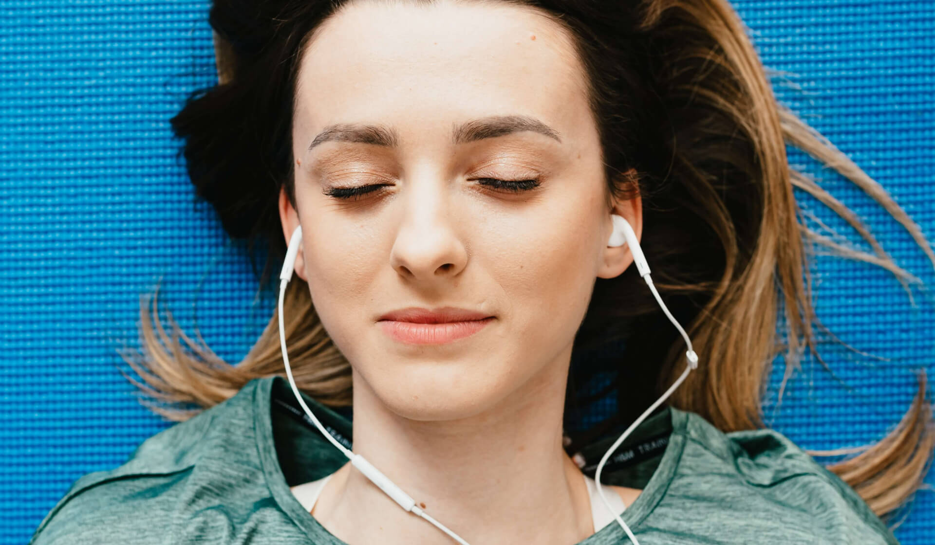 Close up of a woman's face from above, wearing a green shirt and laying on a blue yoga mat with headphones in her ears and her eyes closed, listening to a yoga nidra practice