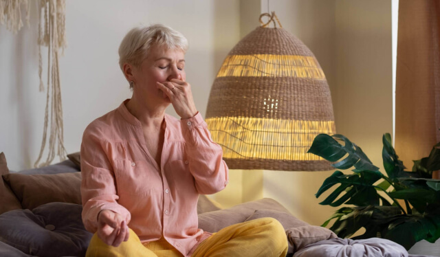 Woman in a pink shirt sitting on a bed with her hand covering one nostril as she practices pranayama