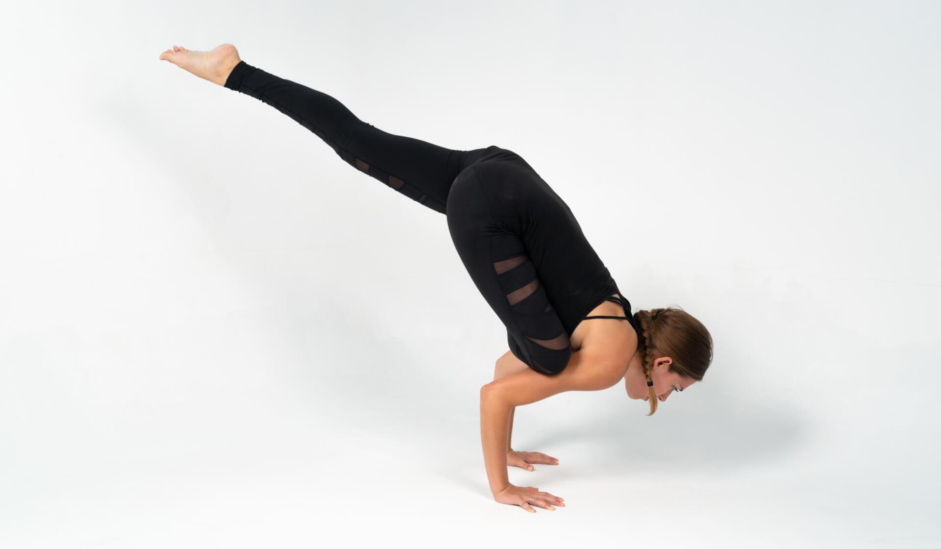 Woman yoga teacher dressed in all black practicing a yoga arm balance pose (flying pigeon pose or eka pada galavasana) against a white backdrop