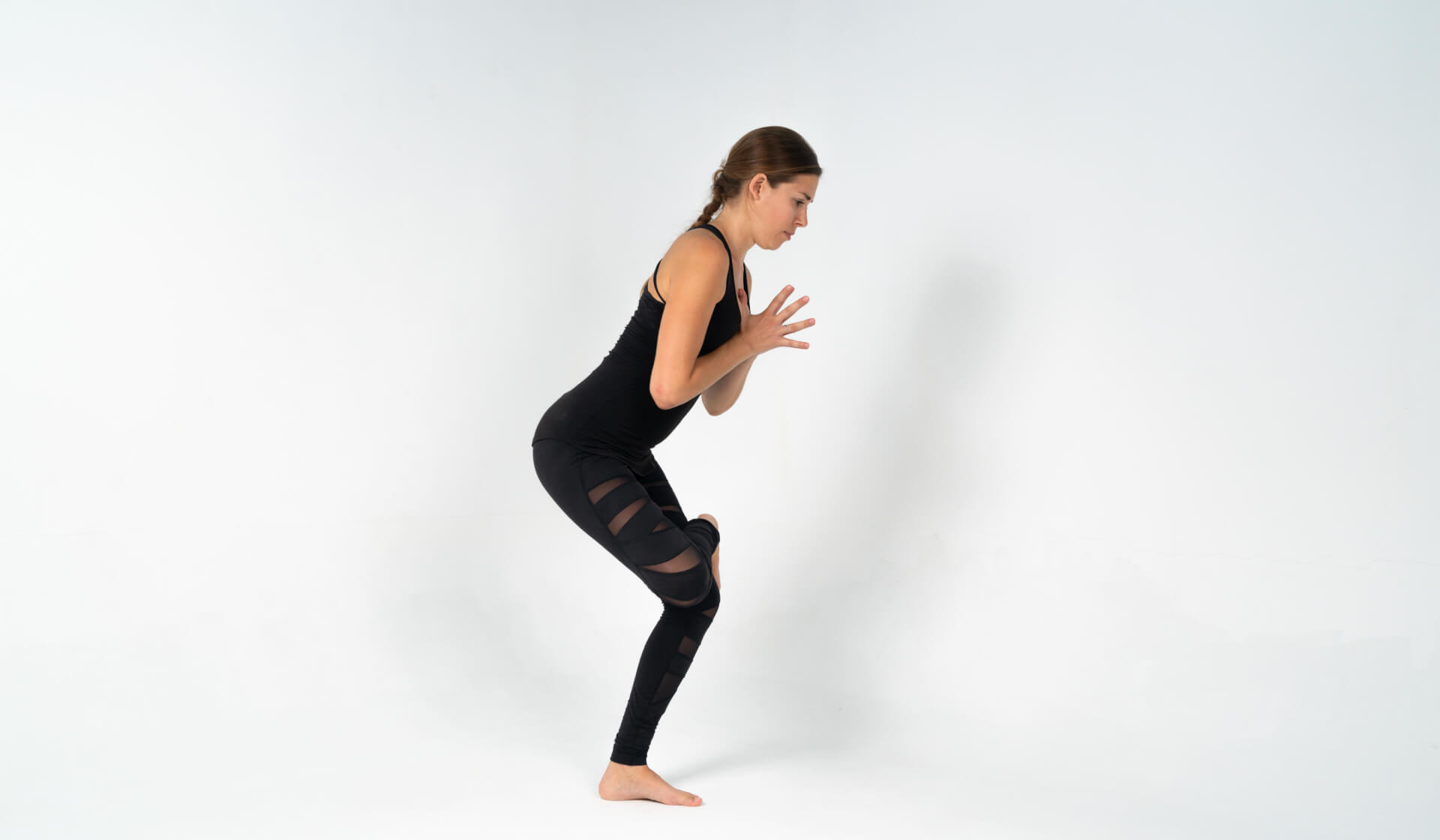 Woman yoga teacher dressed in all black practicing a yoga balance (standing figure-4 pose) against a white backdrop