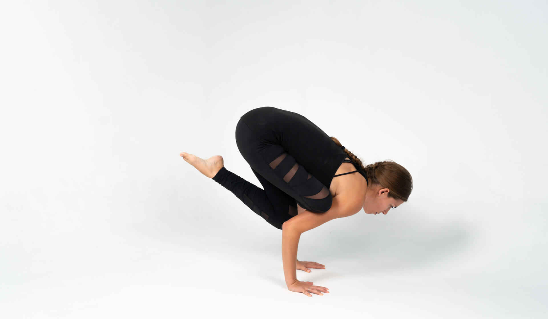 Woman yoga teacher dressed in all black preparing for a yoga pose arm balance (flying pigeon pose or eka pada galavasana) against a white backdrop
