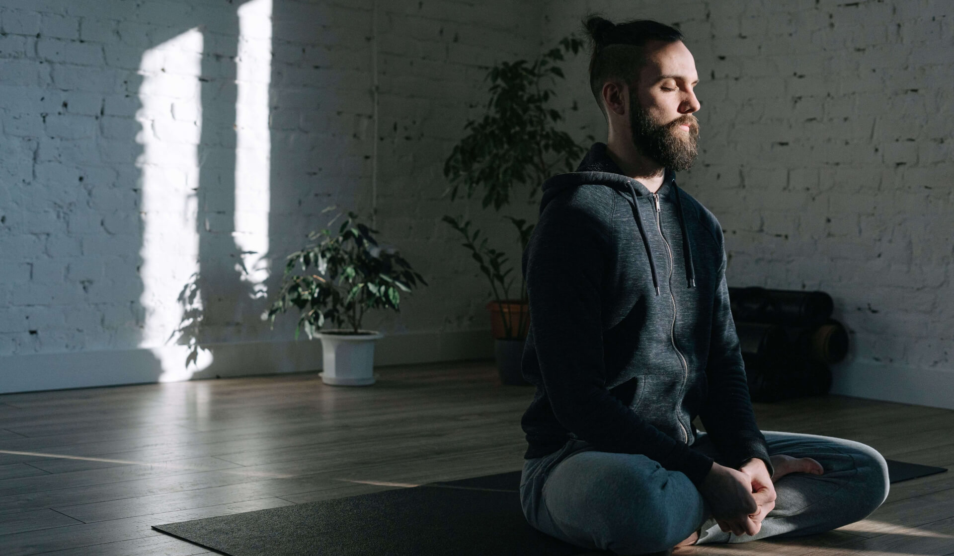 Man with a beard and bun in a hoodie and sweatpants sitting cross-legged on a yoga mat in a dark room with his eyes closed meditating
