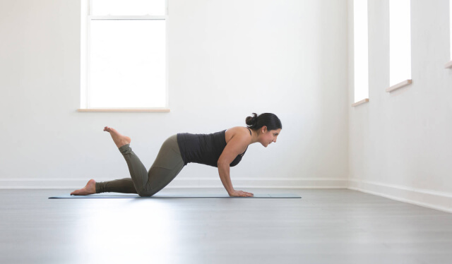 Woman in a black shirt and green yoga pants practicing a modified push-up on a yoga mat in front of a white wall