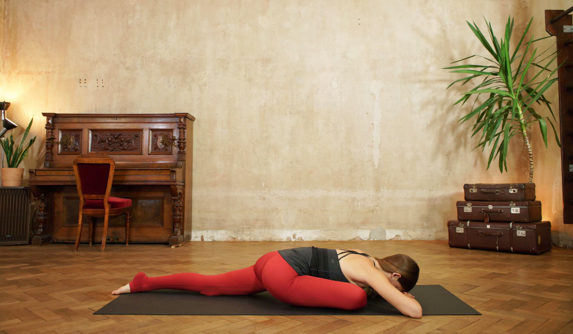 Yoga teacher in black tank top and red yoga pants folding forward into pigeon pose on a black yoga mat in front of a piano, beige wall, stack of suitcases, and green palm tree