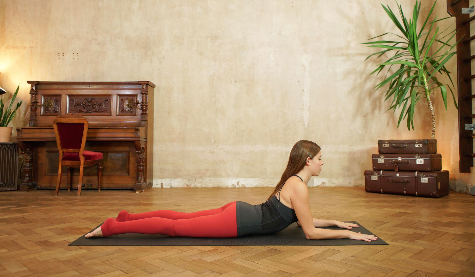 Yoga teacher in black tank top and red yoga pants on her belly in the backbend sphinx pose on a black yoga mat in front of a piano, beige wall, stack of suitcases, and green palm tree