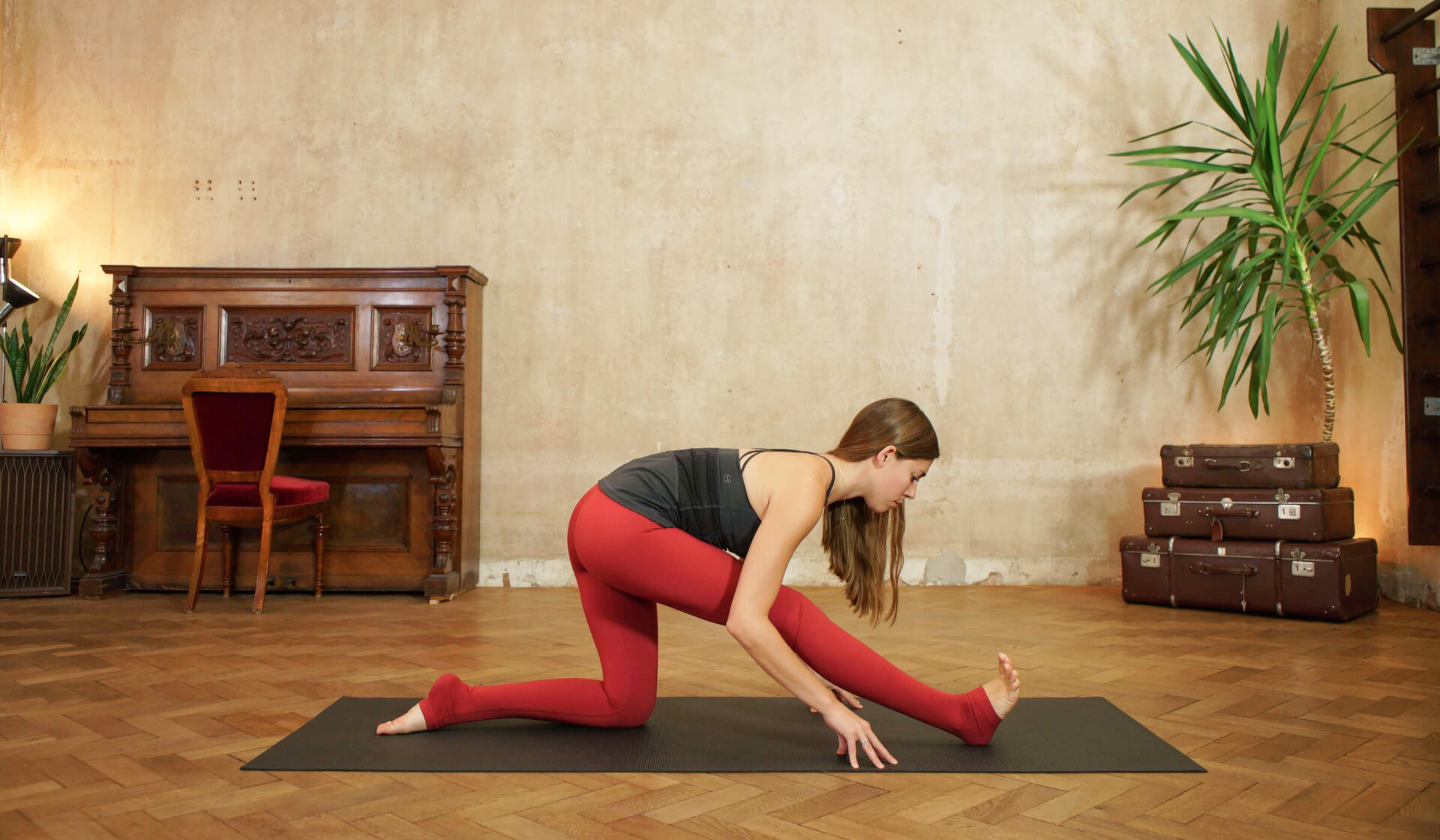 Yoga teacher in black tank top and red yoga pants folding forward into half splits on a black yoga mat in front of a piano, beige wall, stack of suitcases, and green palm tree