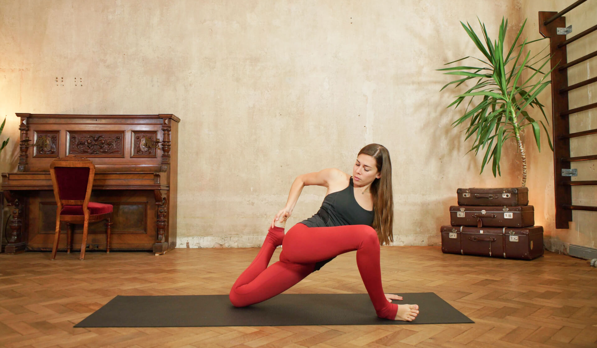 Yoga teacher in black tank top and red yoga pants twisting in a lunge and stretching her quads on a black yoga mat in front of a piano, beige wall, stack of suitcases, and green palm tree