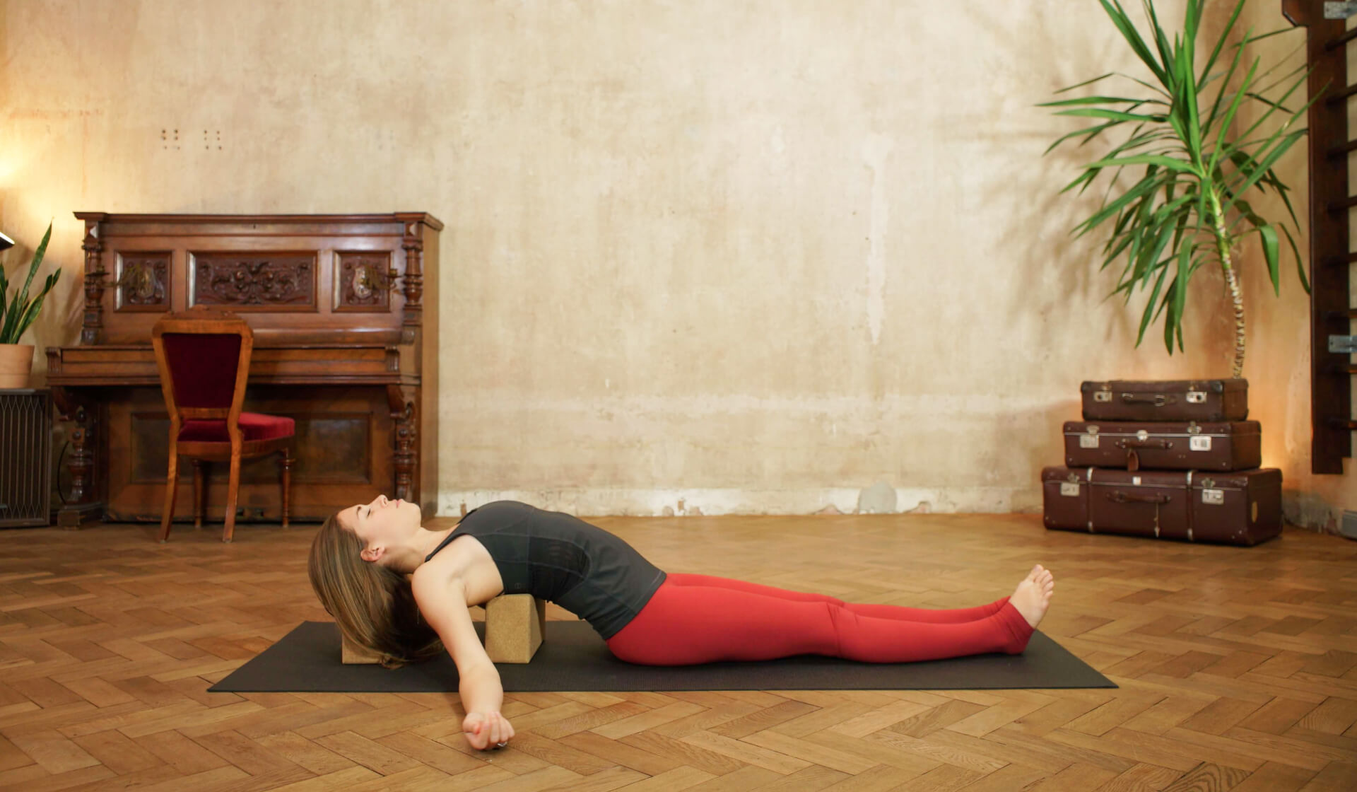 Yoga teacher in black tank top and red yoga pants laying back over yoga blocks into supported fish pose on a black yoga mat in front of a piano, beige wall, stack of suitcases, and green palm tree