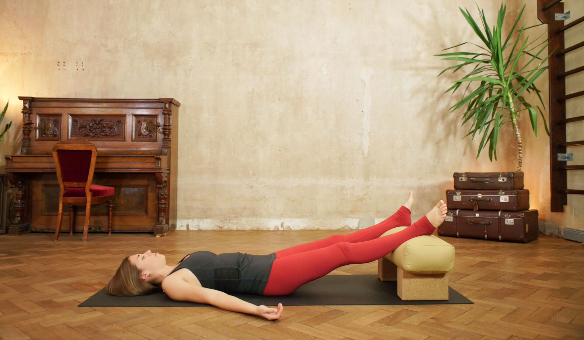 Yoga teacher in black tank top and red yoga pants laying down with her feet on a yoga bolster on a black yoga mat in front of a piano, beige wall, stack of suitcases, and green palm tree