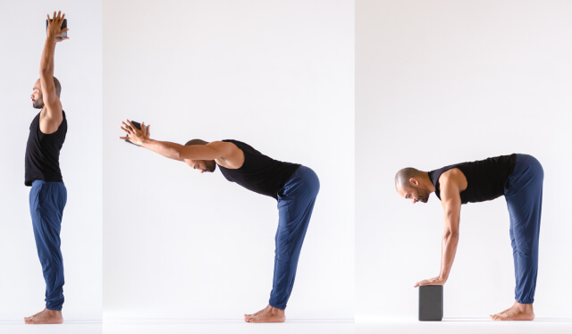 Male yoga teacher in blue pants and a black tank top holding a yoga block overhead and then swan diving to fold forward with the block in his hands