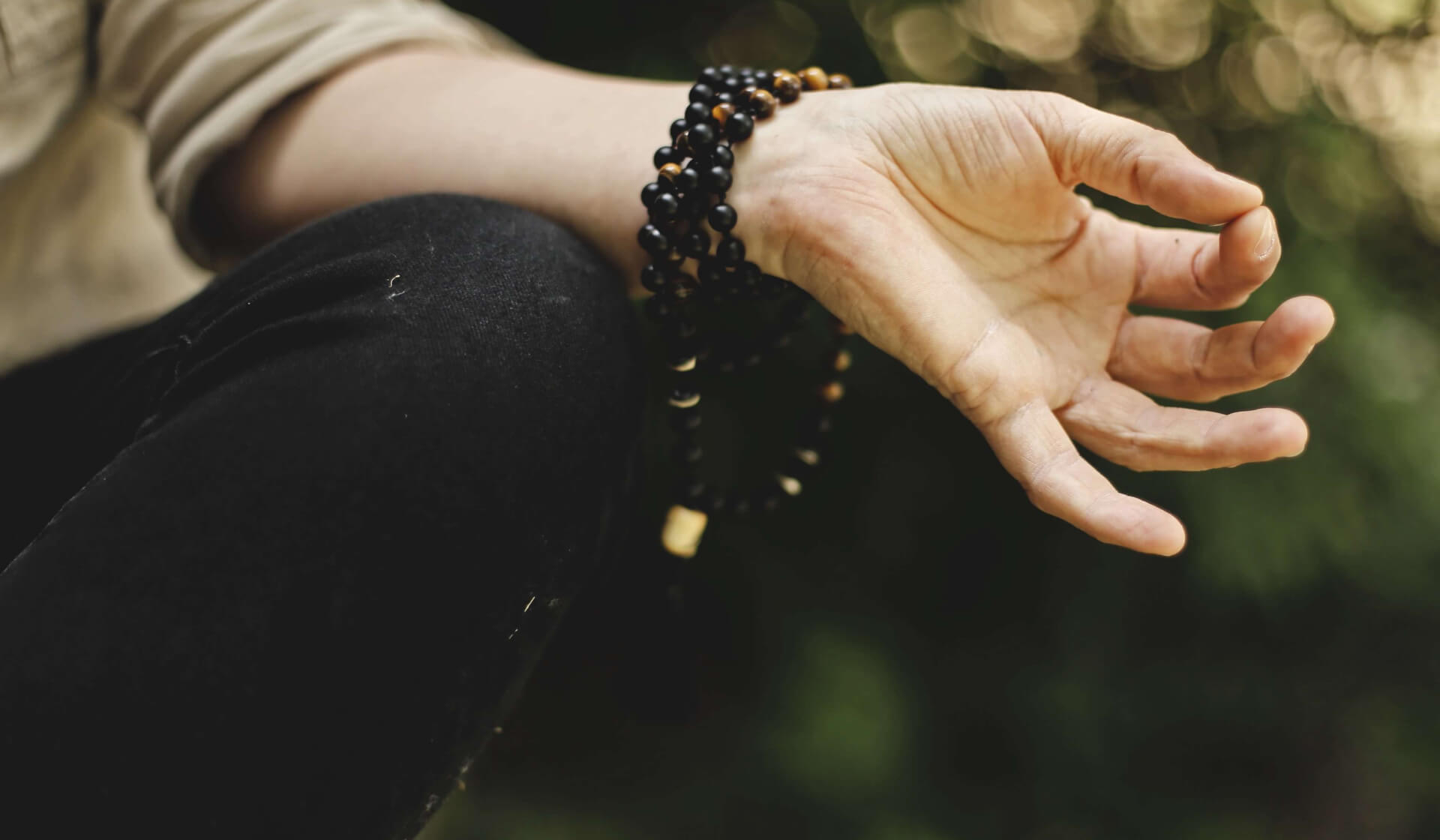 Close-up of a women's knee and hand as she sits crossed-legged in meditation making a mudra with her fingers with mala beads wrapped around her wrist