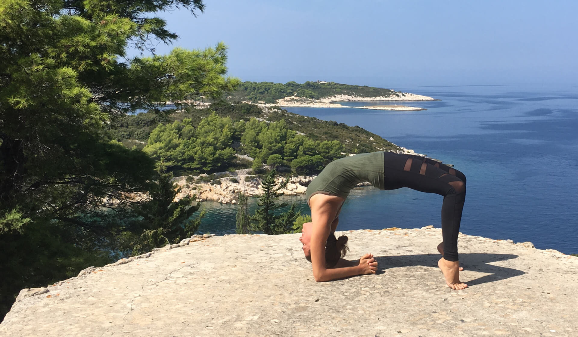Woman yoga teacher in black pants and a green tank practicing a deep backbend in front of an ocean view and trees